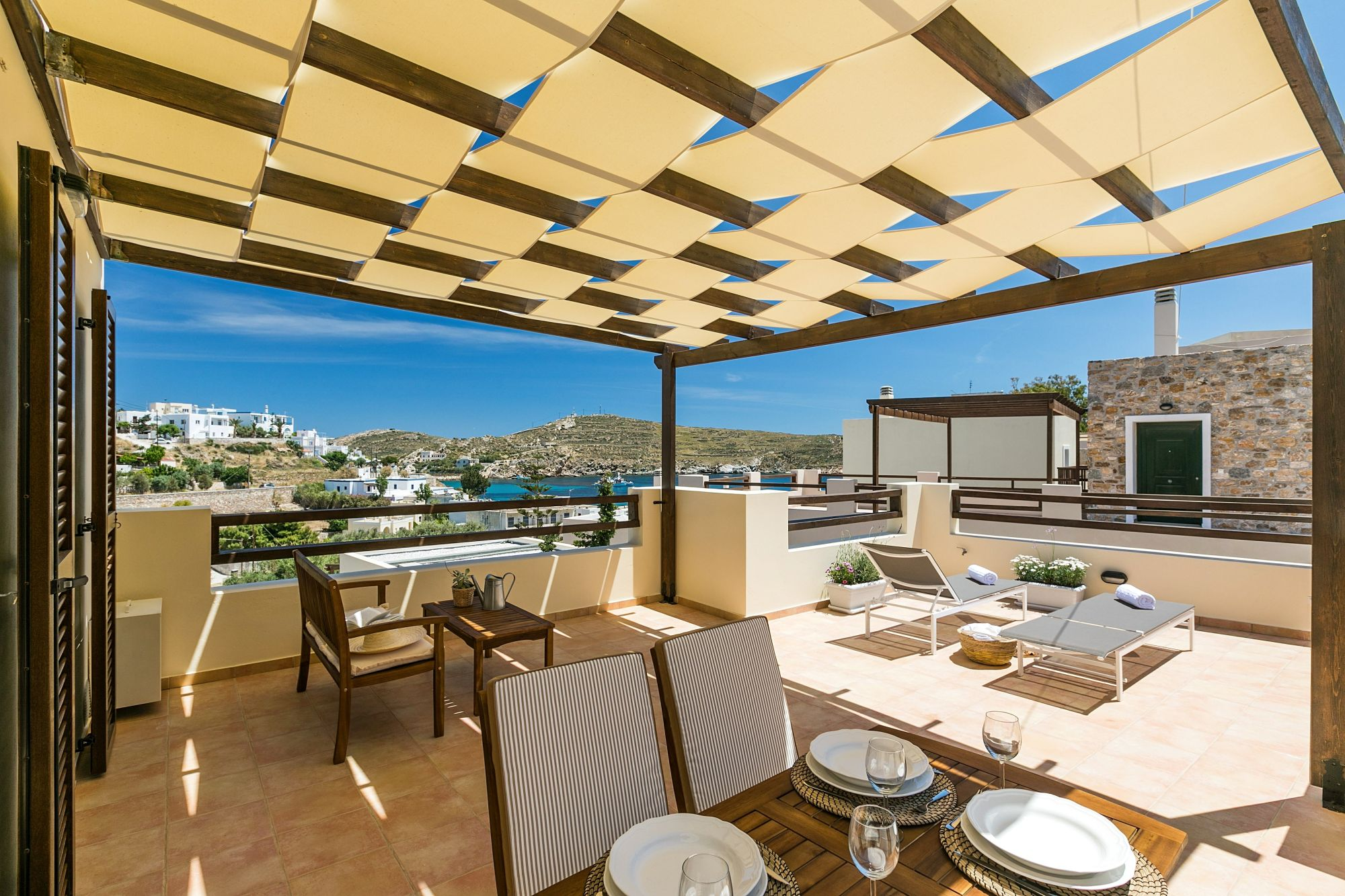 A spacious sea view veranda with pergola, furnished with lounge, two sunbeds and dining table.