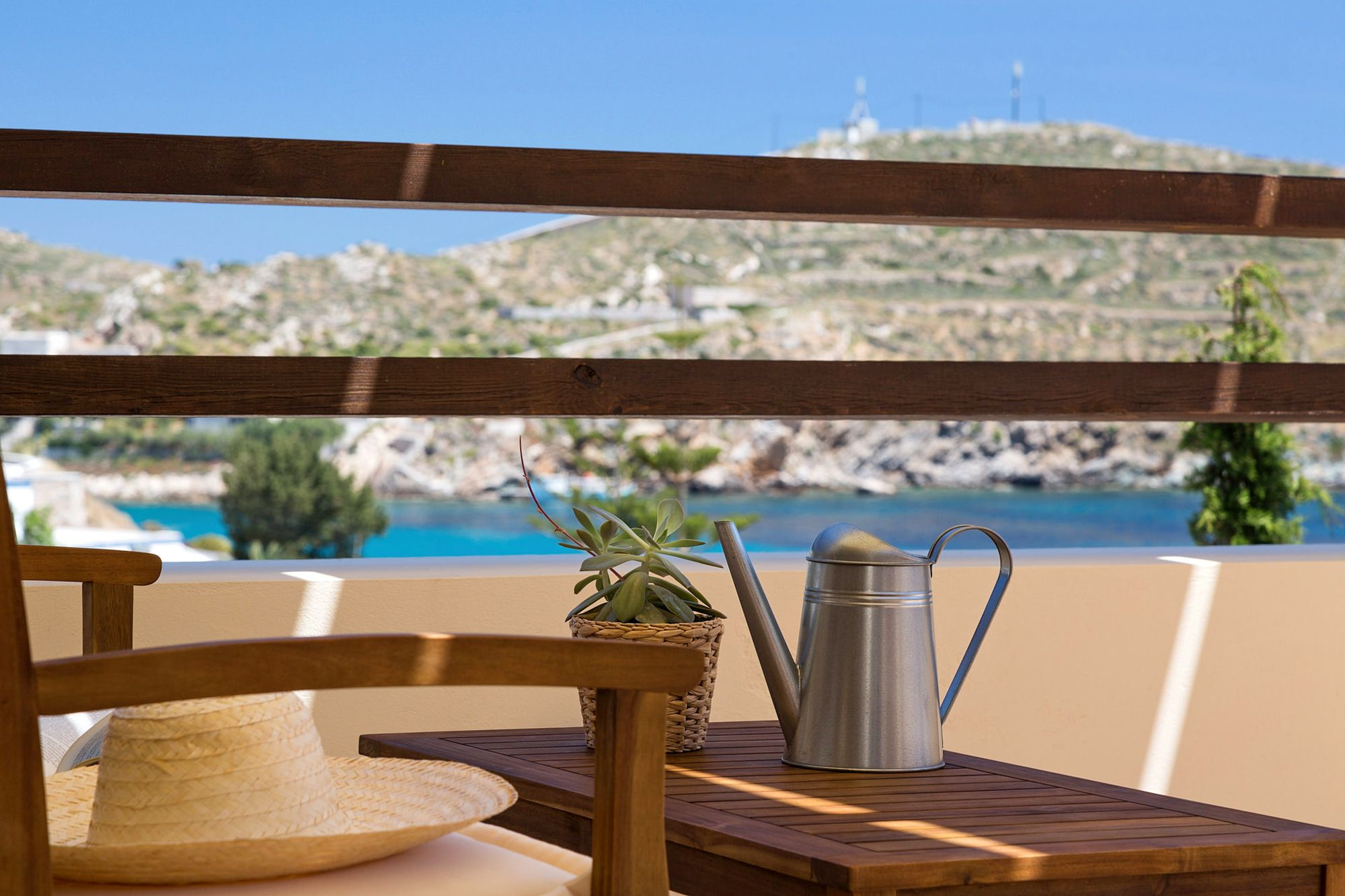 The sea view from a Syra Suite veranda furnished with an exterior sofa and a coffee table with a small decorative watering can on it.