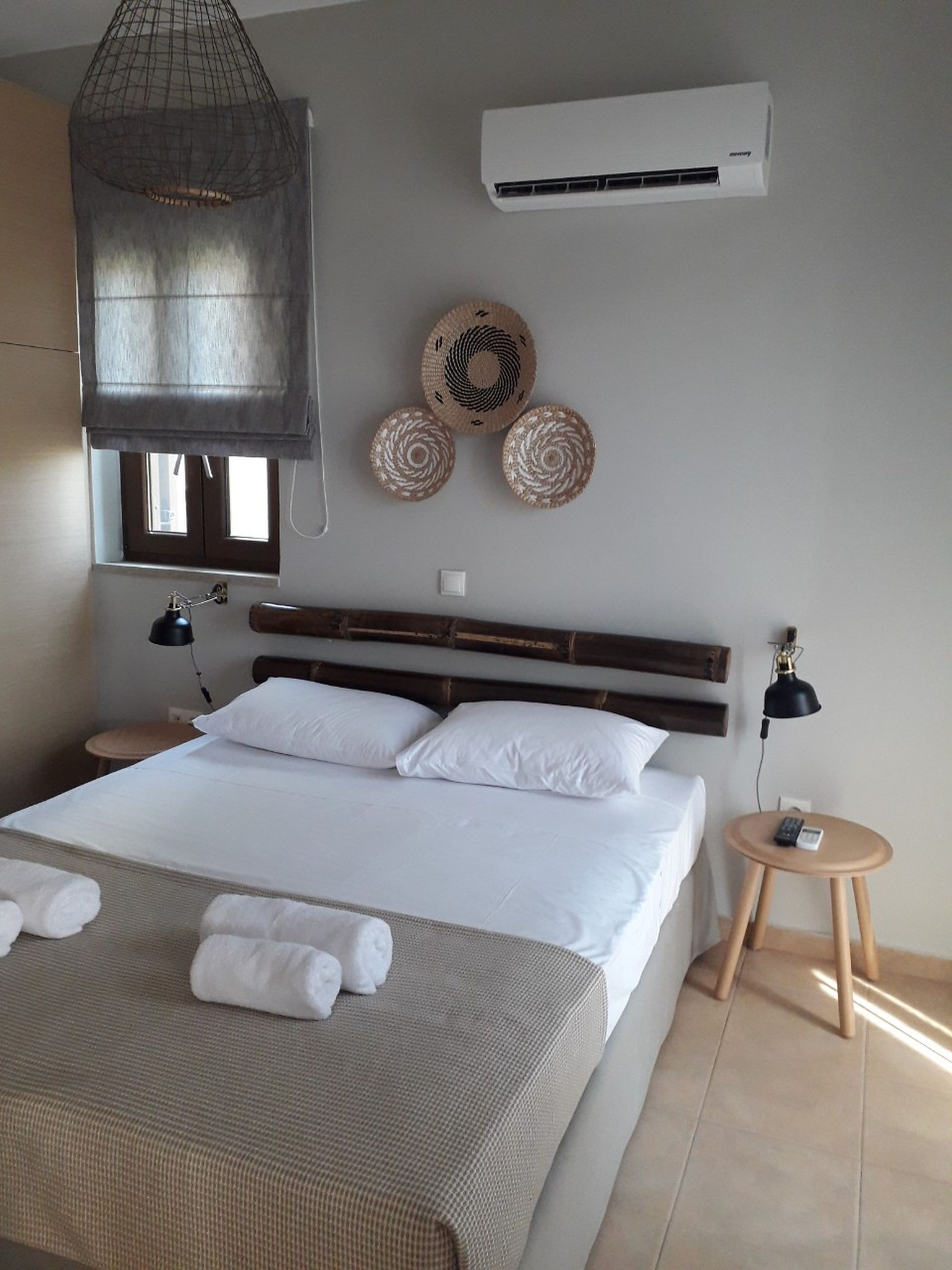 An air-conditioned bedroom with a double bed decorated with bamboo masts over the bed and three wicker round deco elements on the wall.