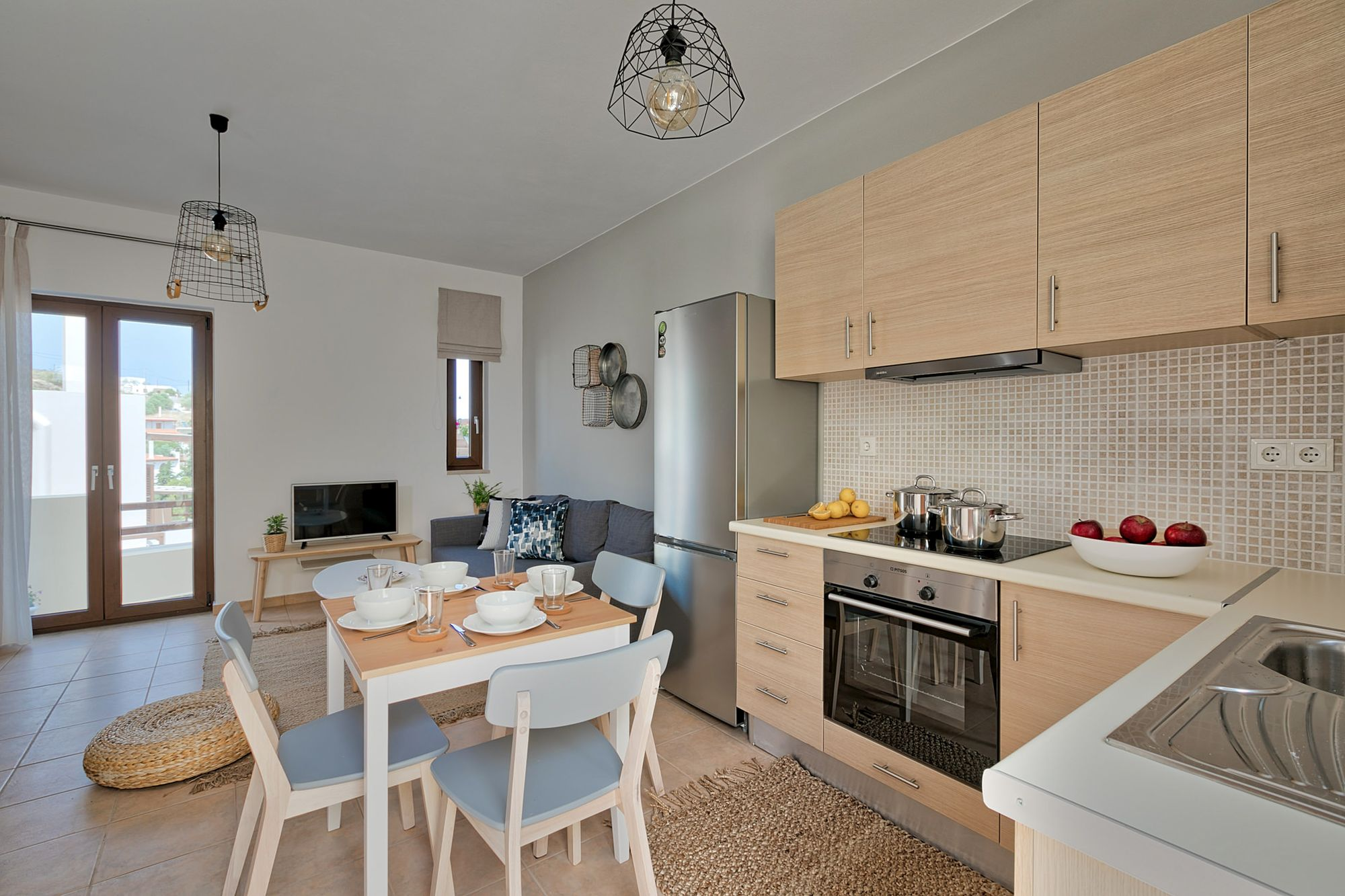 In open space with the living room, a fully equipped kitchen with an inox fridge, an electric cooker oven and a dining table with modern white dinnerware on it.