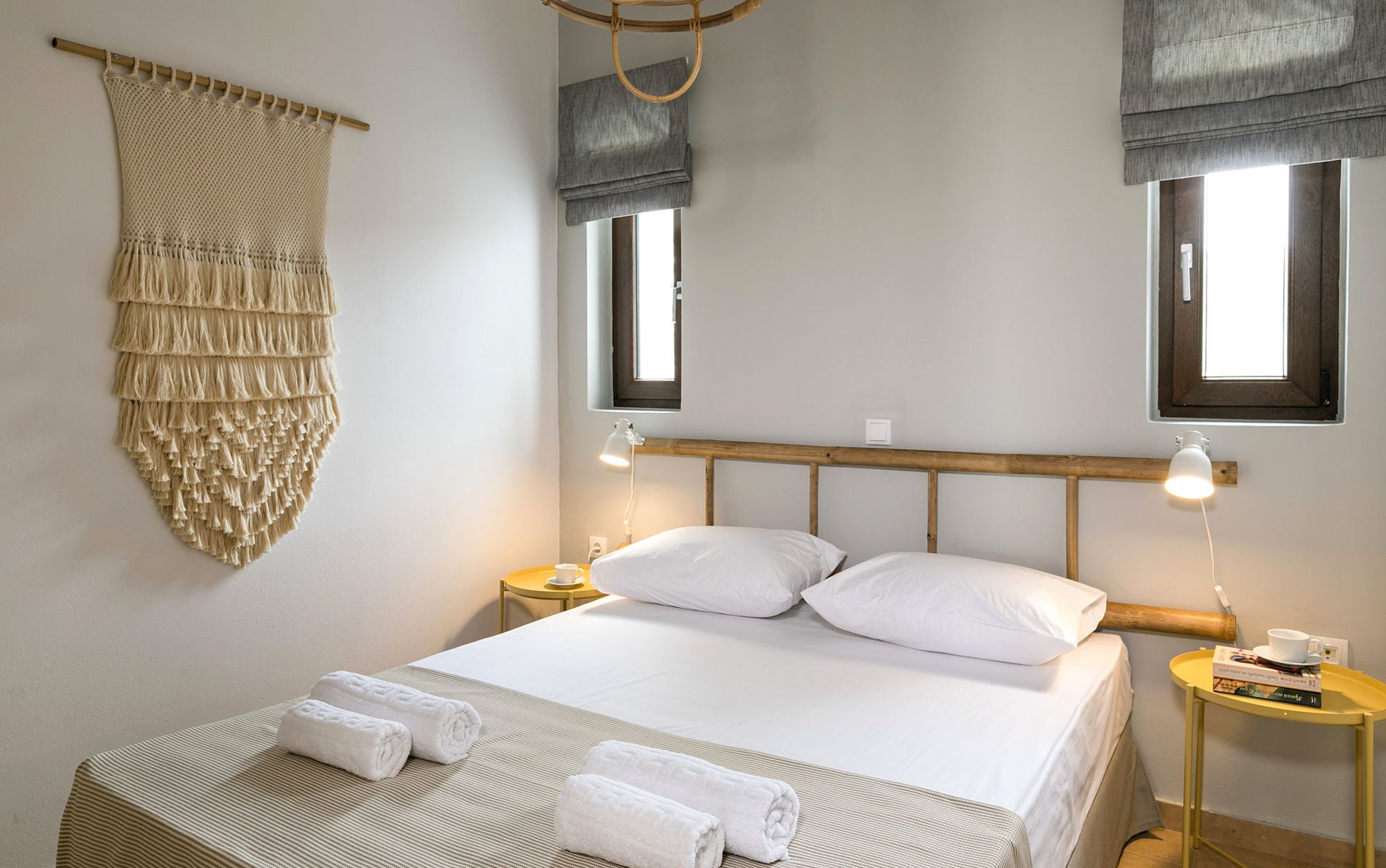 Syra Suite bedroom with a double bed, metallic yellow bedside tables, modern white wall lights, two windows on the wall over the bed and boho decoration with a wooden ladder over the bed and a big macramé.