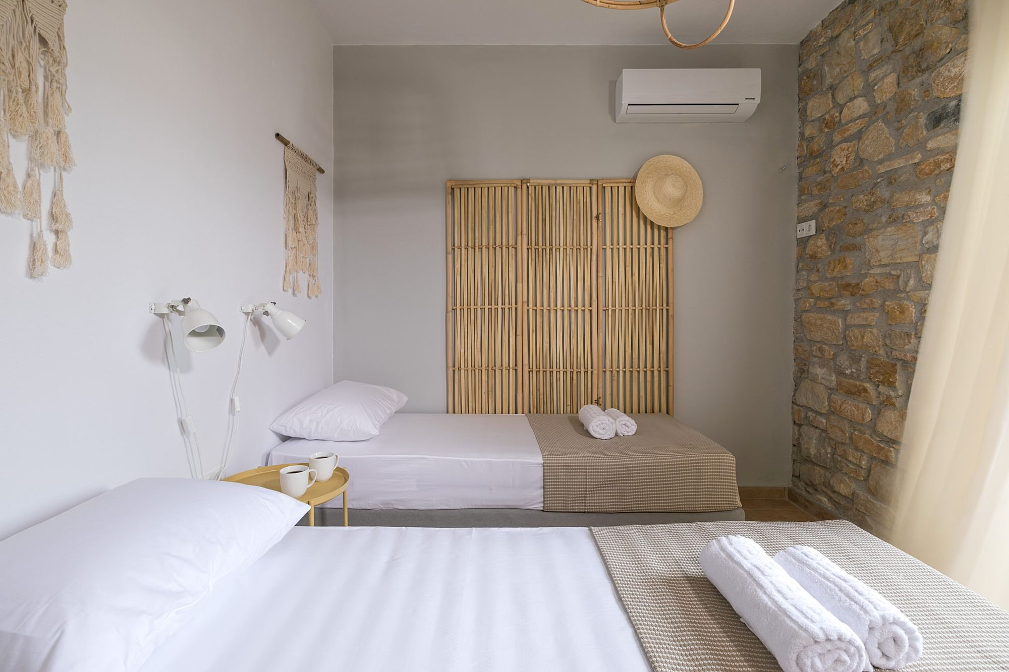 A twin bedroom of a stone-built residence decorated in boho style and in earth tones.