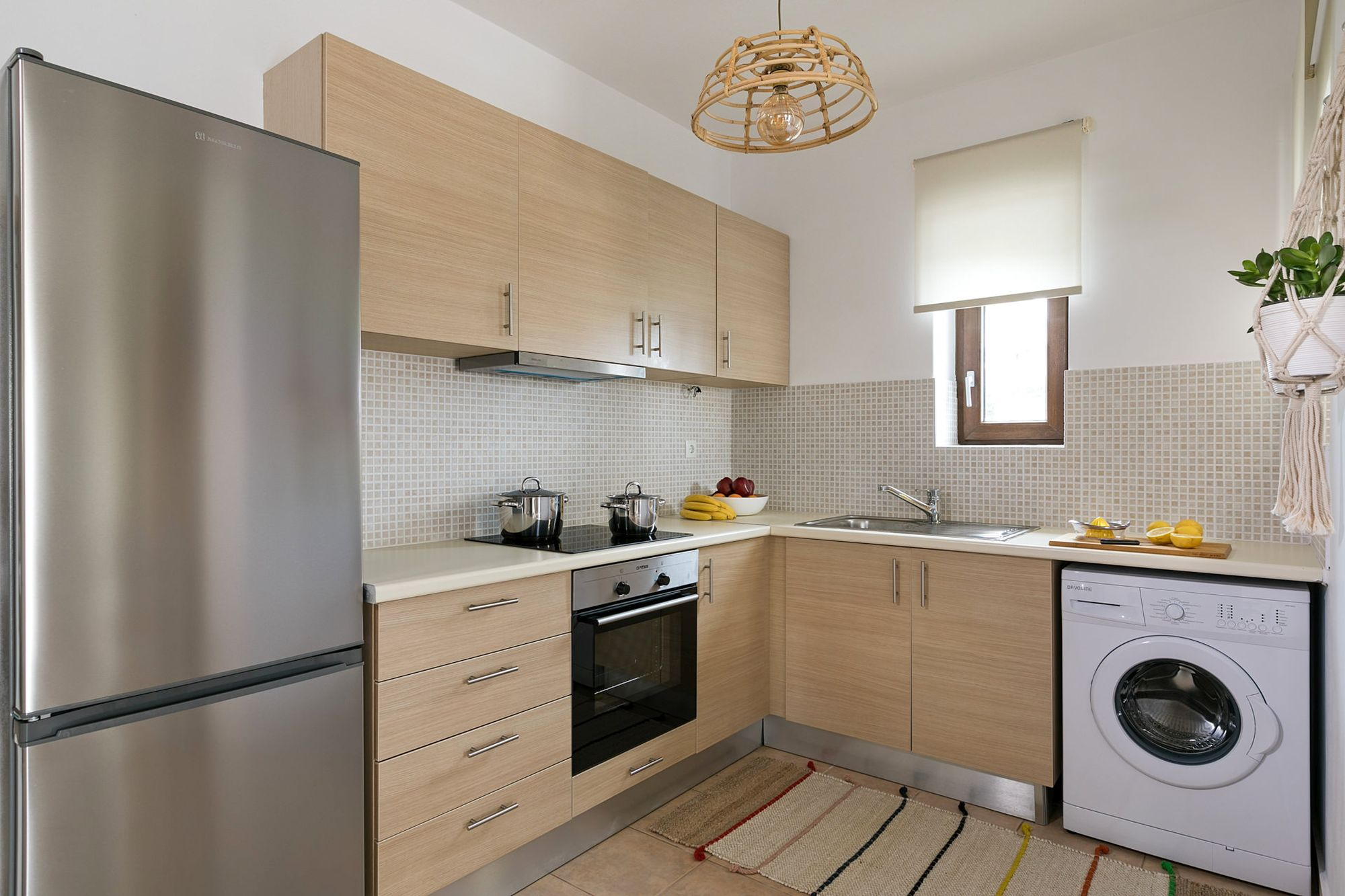 Modern kitchen with beige cabinets, a big inox fridge, an electric cooker oven and a washing machine.