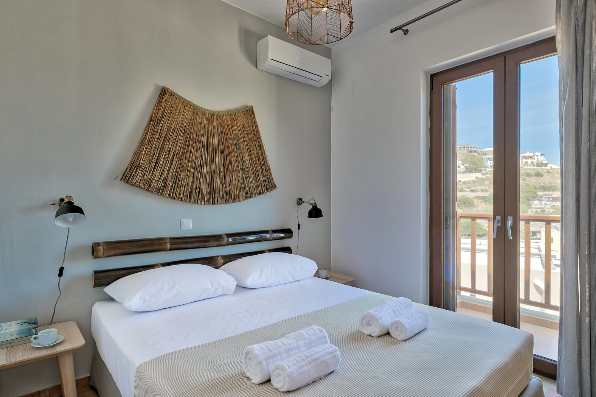 Air-conditioned bedroom with double bed, black wall lights, wooden bed side tables, a big wall wicker deco element and wooden bamboo masts over the bed.