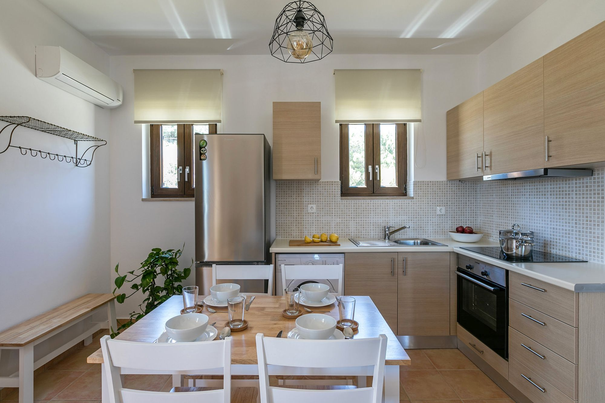 Syra Suites modern kitchen with beige cabinets, fully equipped with a big inox fridge, an electric cooker oven, a wooden bench and wooden dining table with four white chairs.