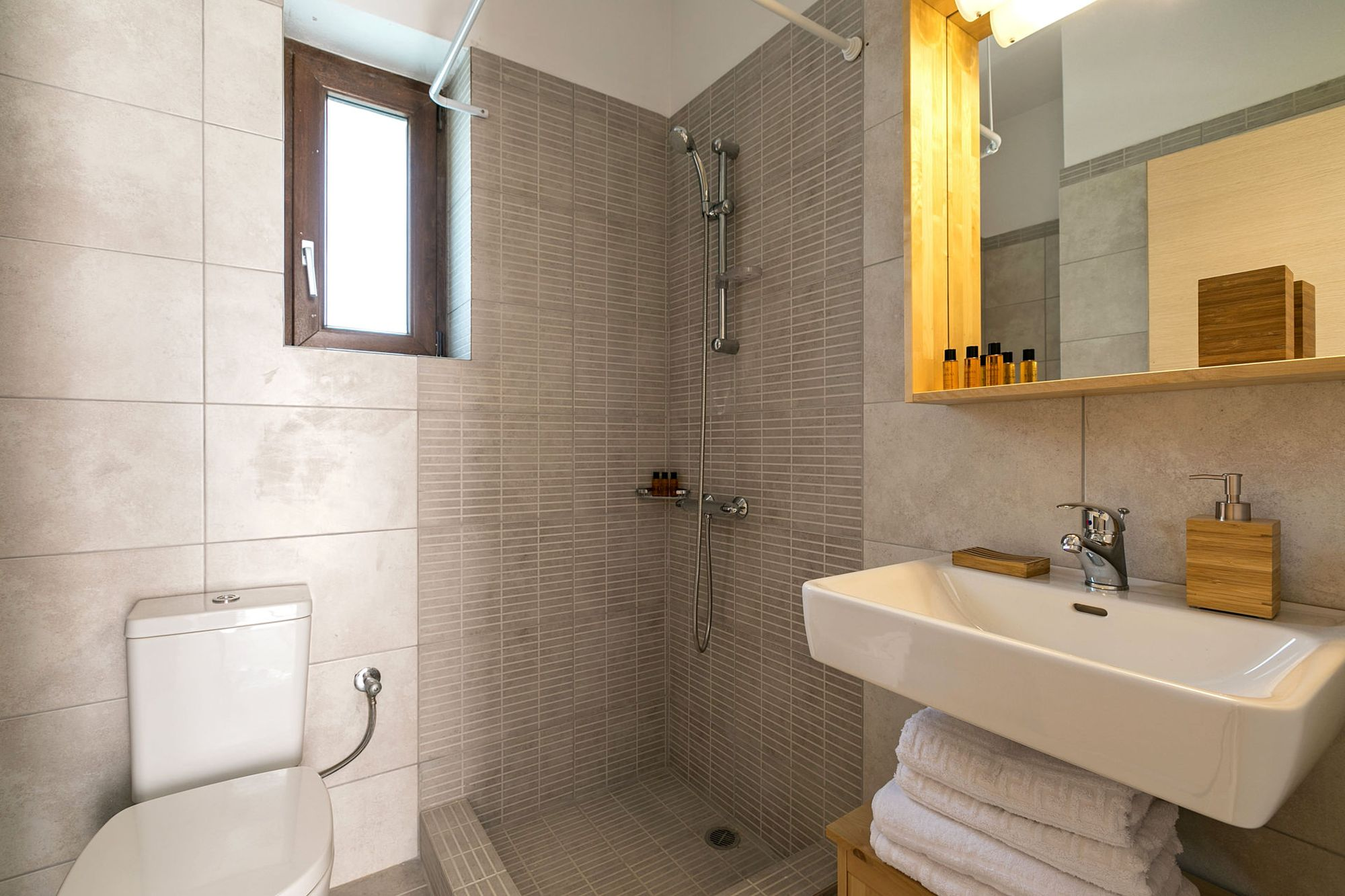 Beige bathroom with shower, a big white washbasin and a big wooden mirror.