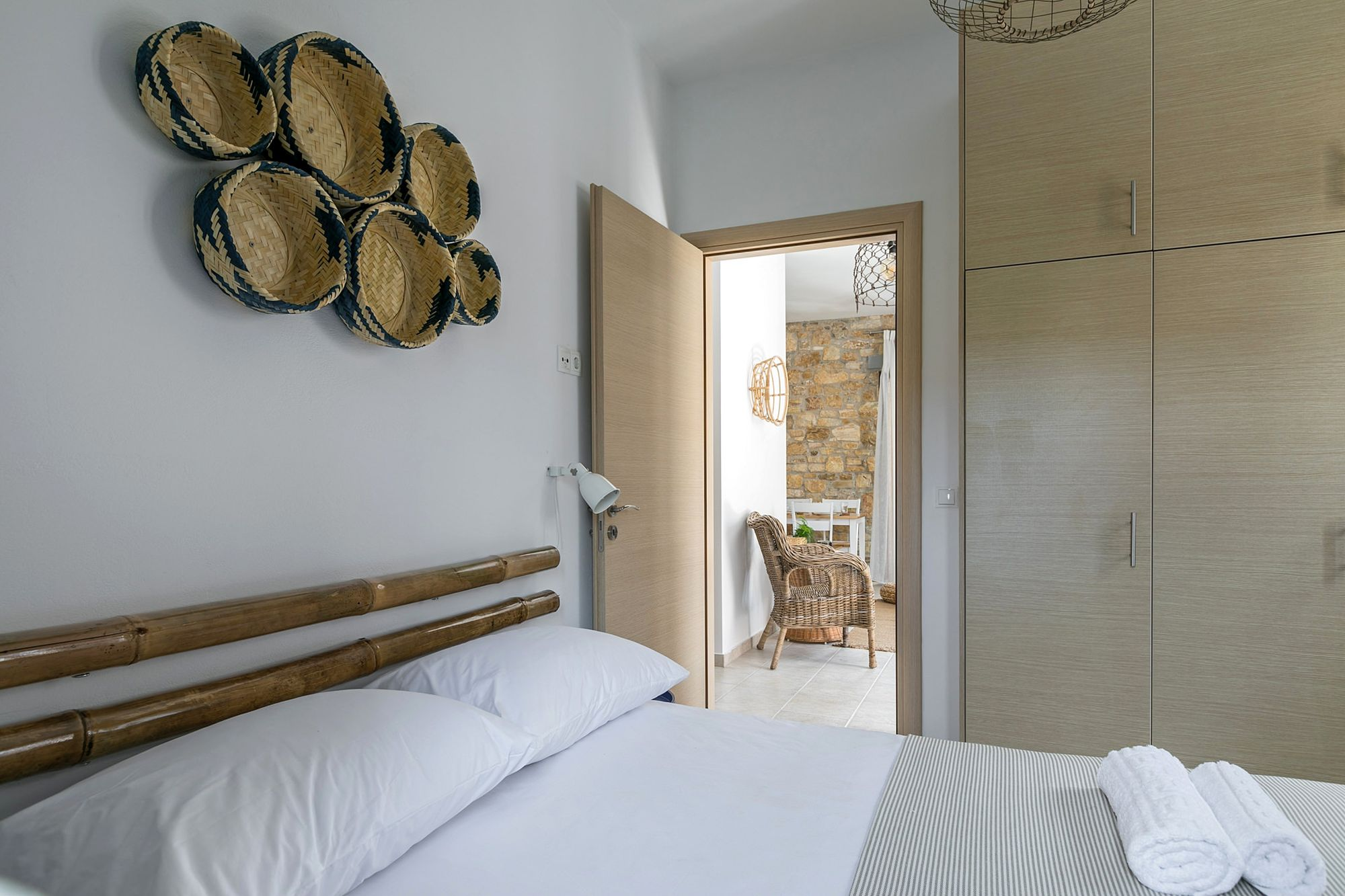 Bedroom with a double bed and decoration with bamboo masts and wicker objects on the wall over the bed.