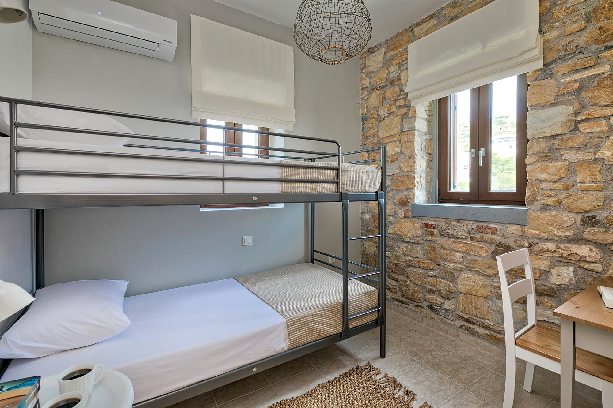 Twin stone-built bedroom with bunk beds, a bedside table and a small desk.