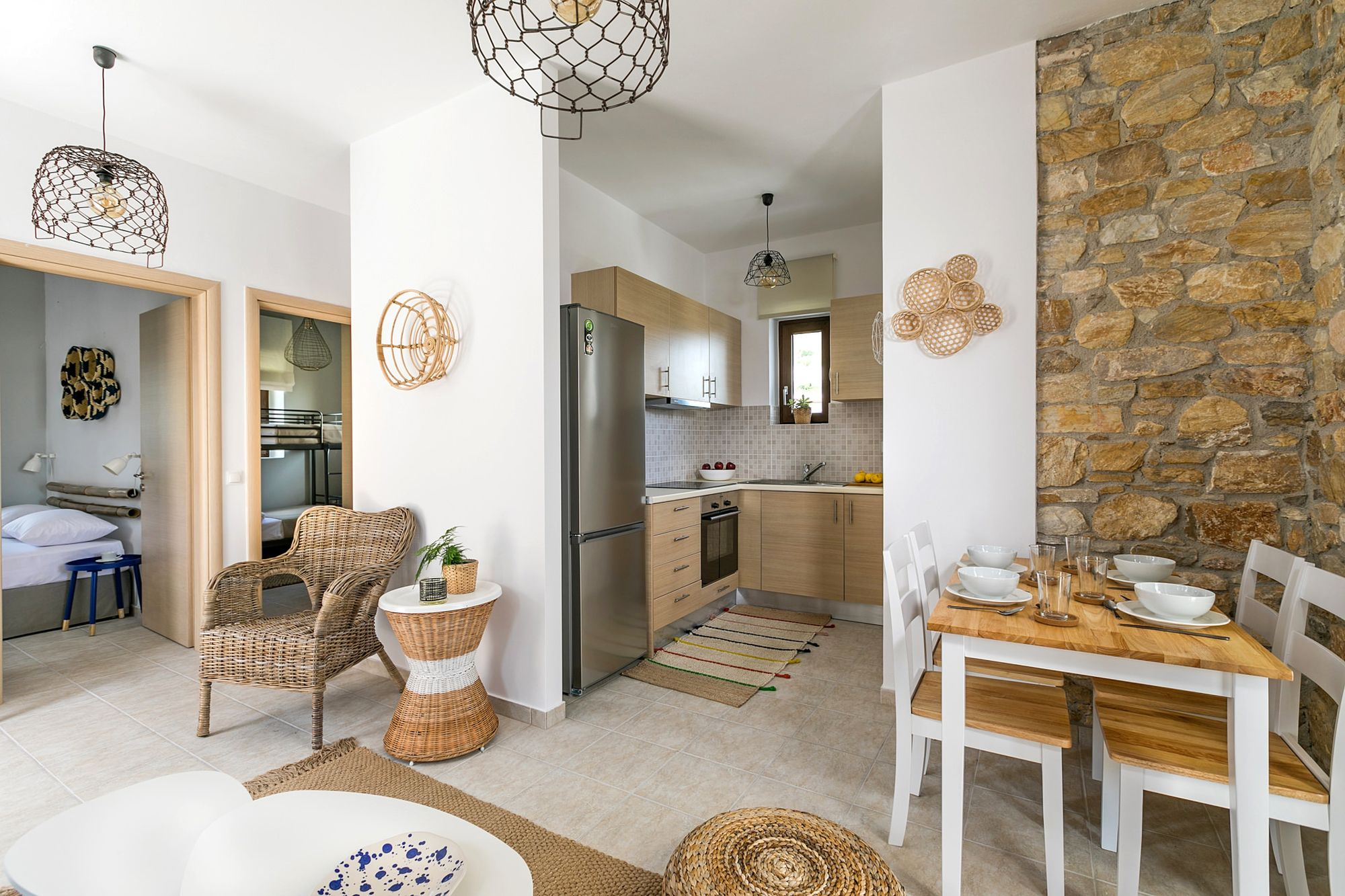 A stone-built residence decorated in boho style with two bedrooms, one with a double bed and a second one with bunk beds, a kitchen and a dining table with four chairs.