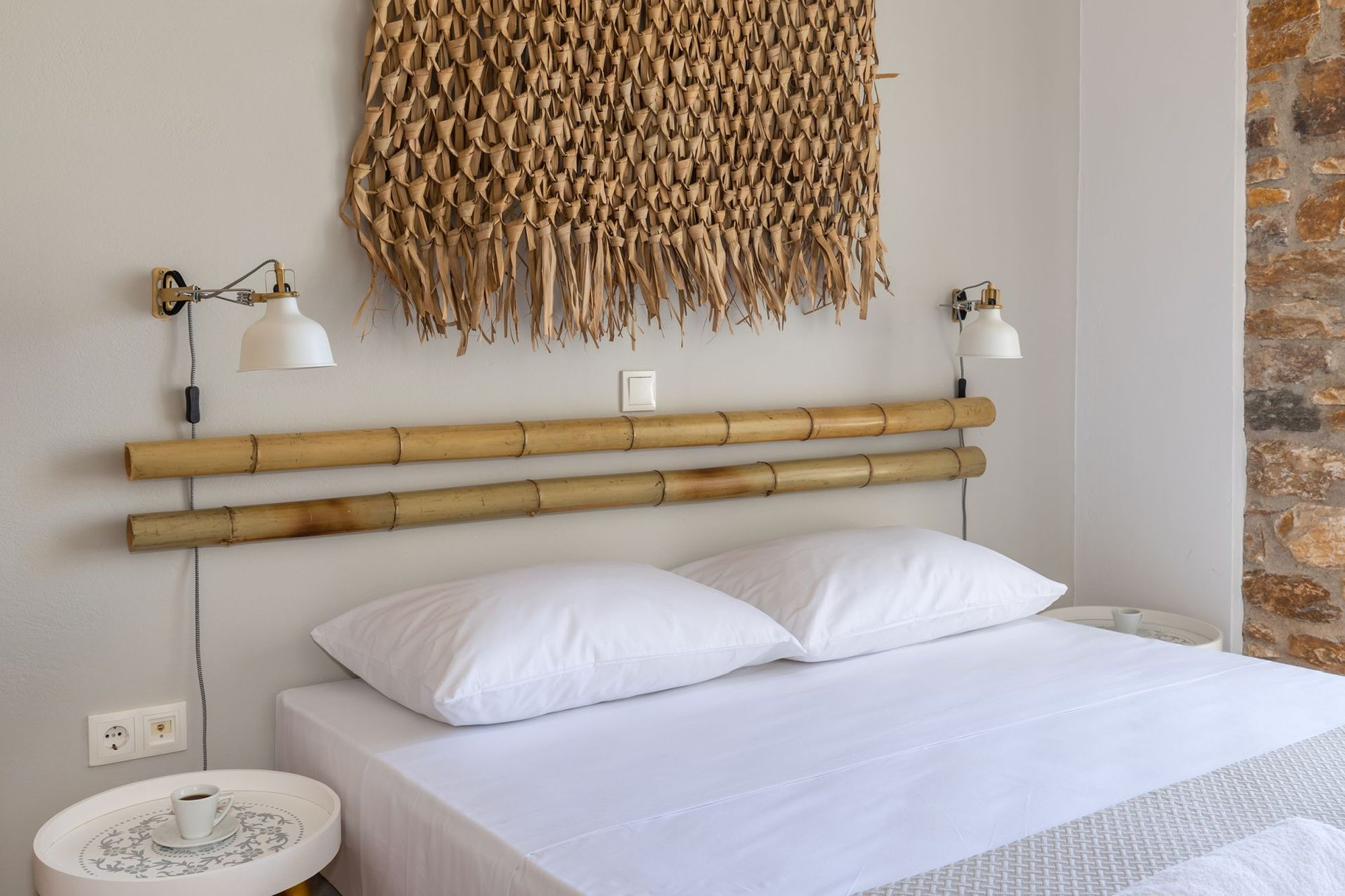 A double bed with white sheets in a stone-built bedroom, two white bedside tables, two gold-white wall lights and the wall over the bed is decorated with bamboo masts and a wicker decorative element.