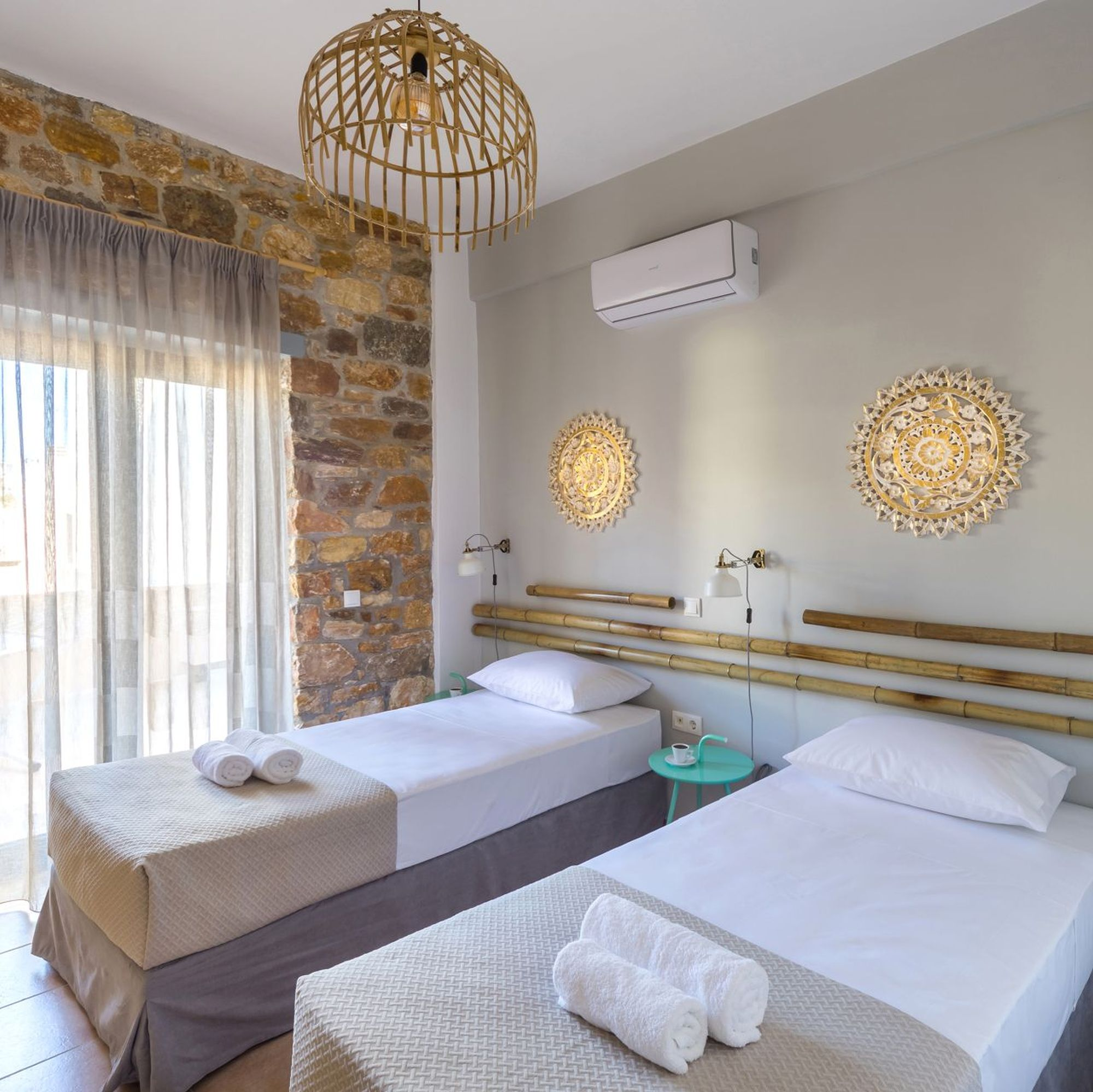 Twin bedroom of a stone built Syra Suite residence, blue bedside tables, white-gold wall lights, decorative masts and round gold metallic decorative elements on the wall over the beds.