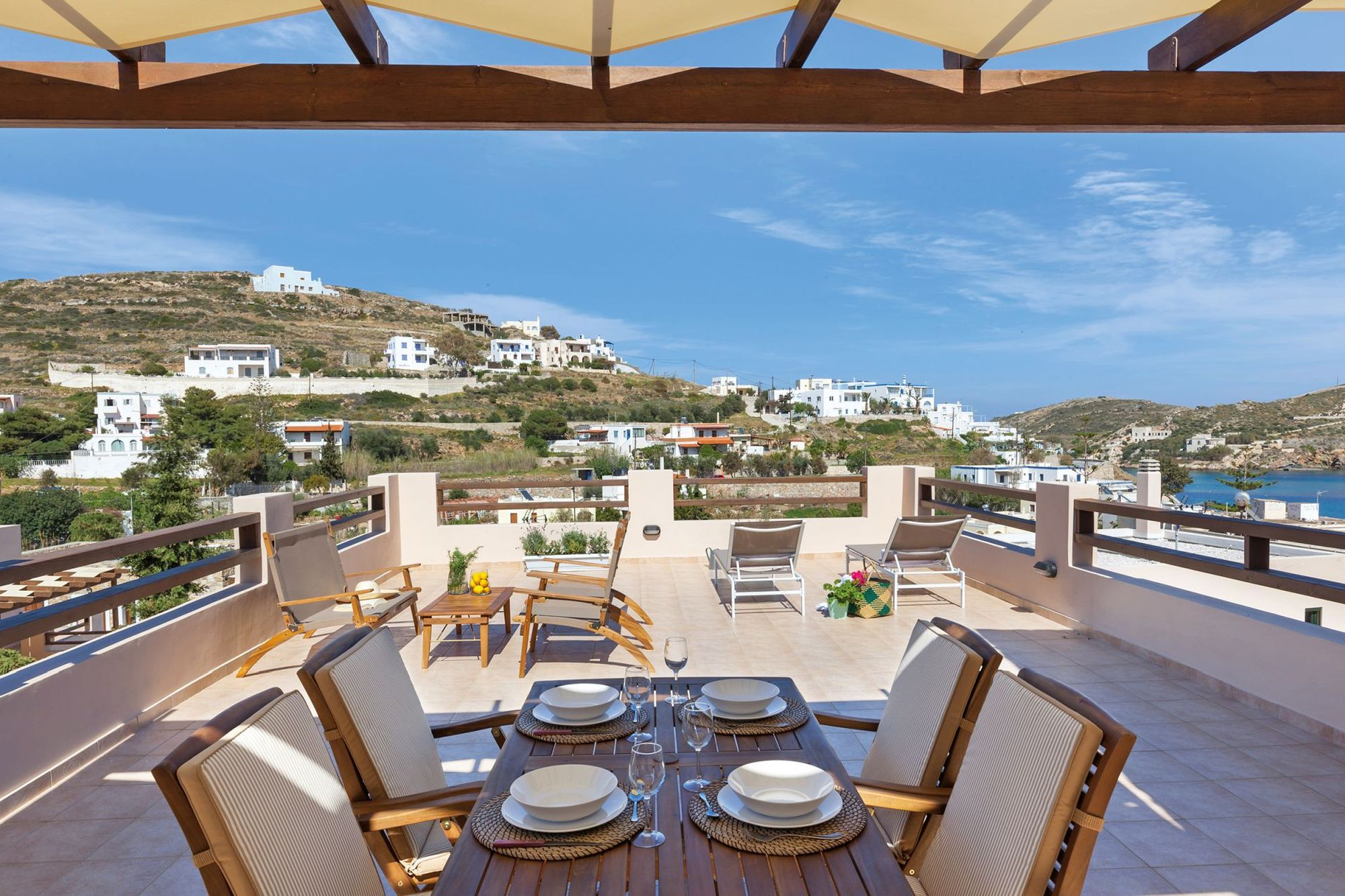 Spacious sea view veranda with pergola fully furnished with a dining table, a lounge and two sunbeds.