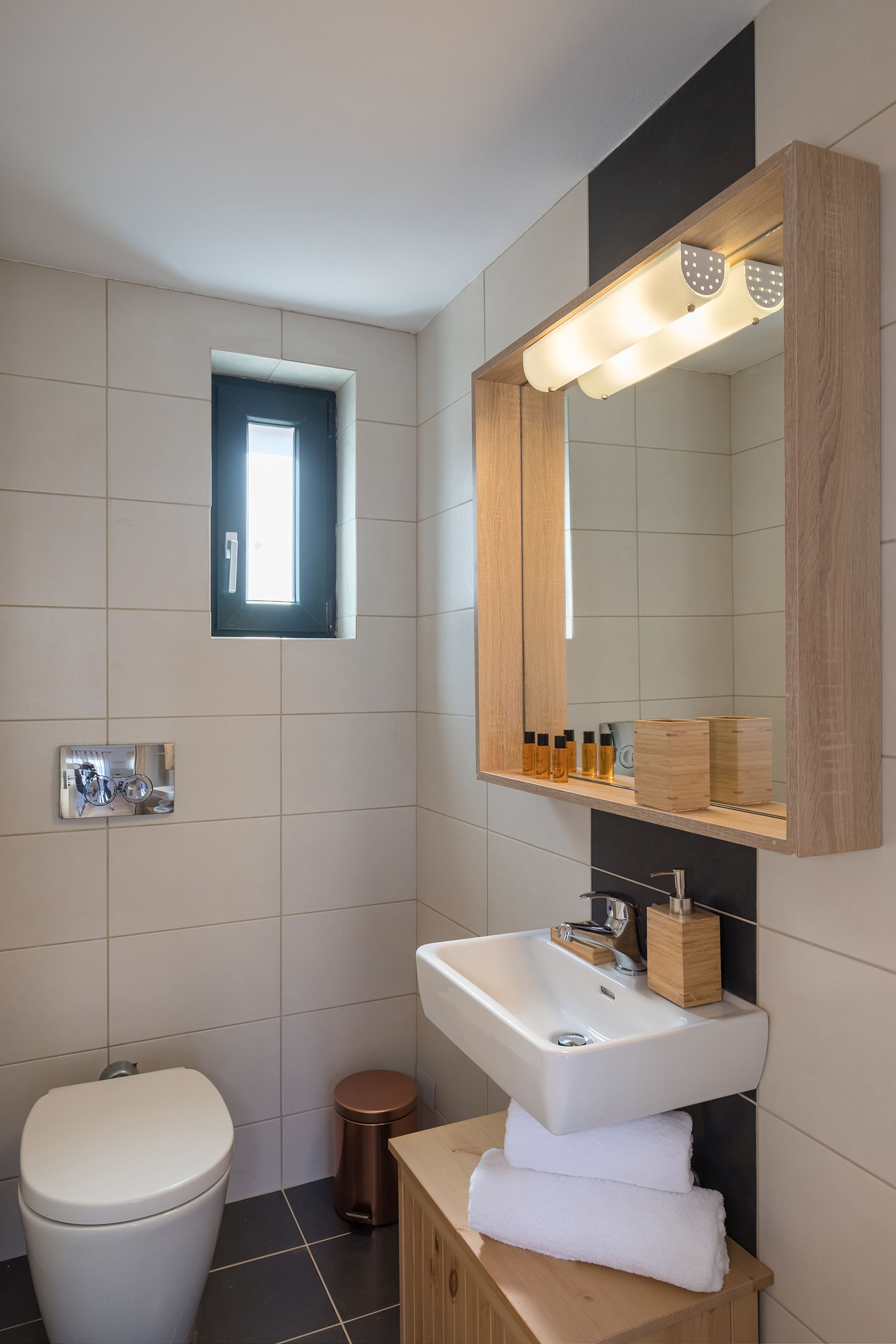 Bathroom with white and gray tiles, a white washbasin and a big wooden mirror.