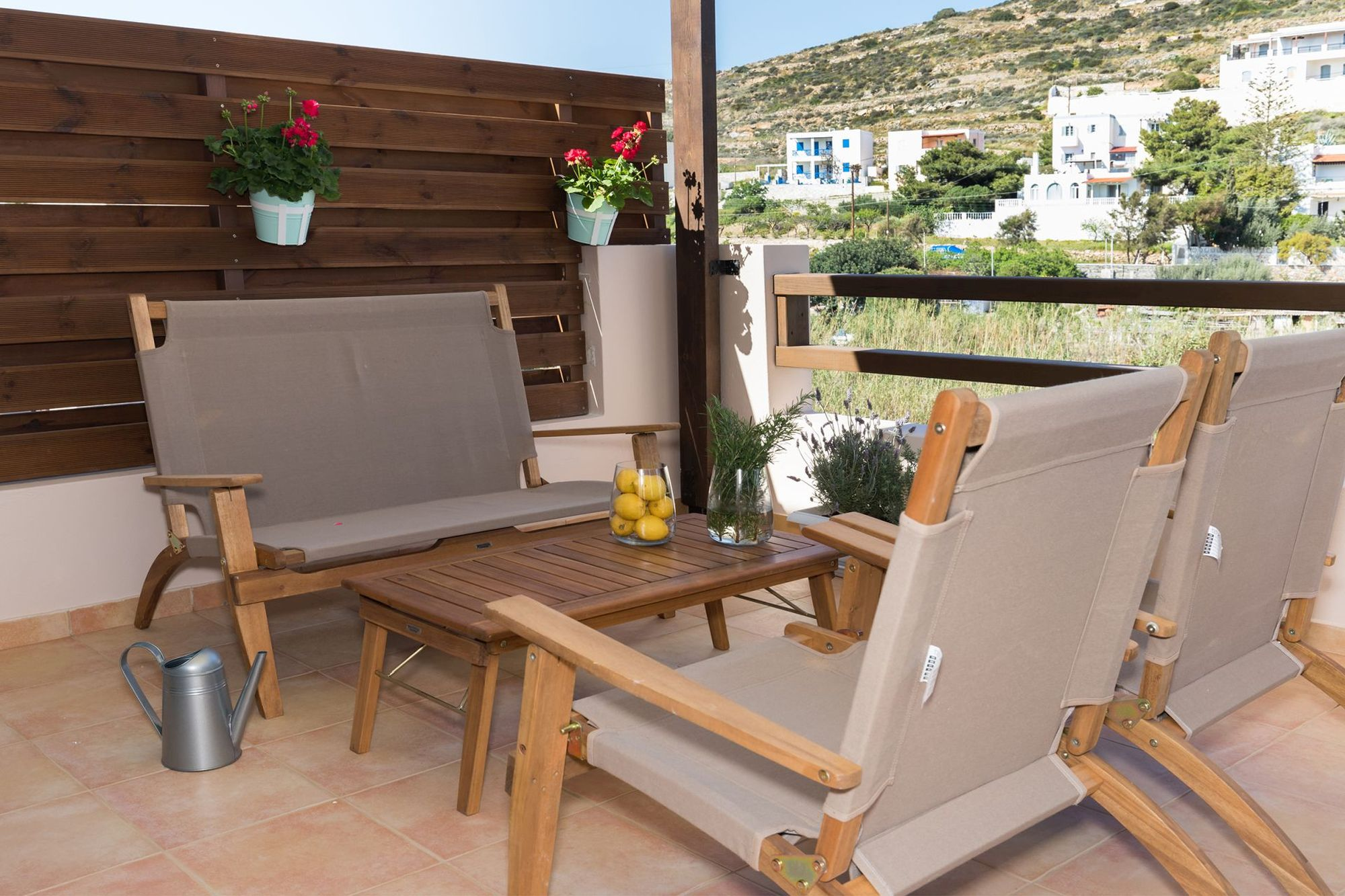 Veranda with beautiful flowerpots furnished with a sofa, a coffee table and two armchairs.