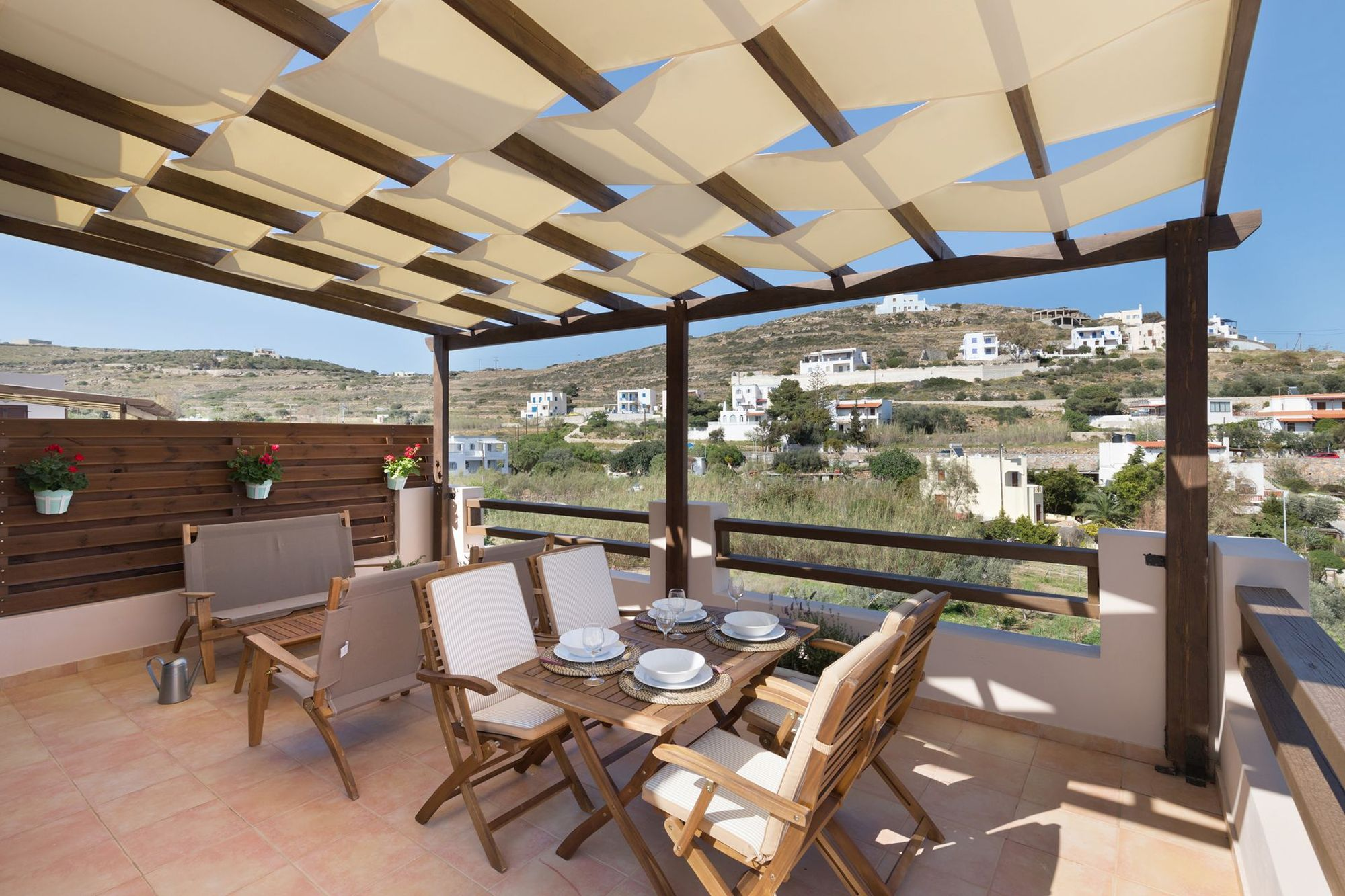 Veranda with pergola furnished with lounge and dining table with four chairs.