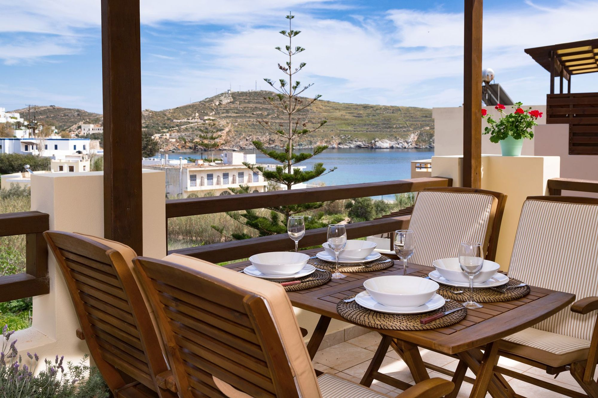 Sea view veranda with a dining table for four persons with white dinnerware on it.