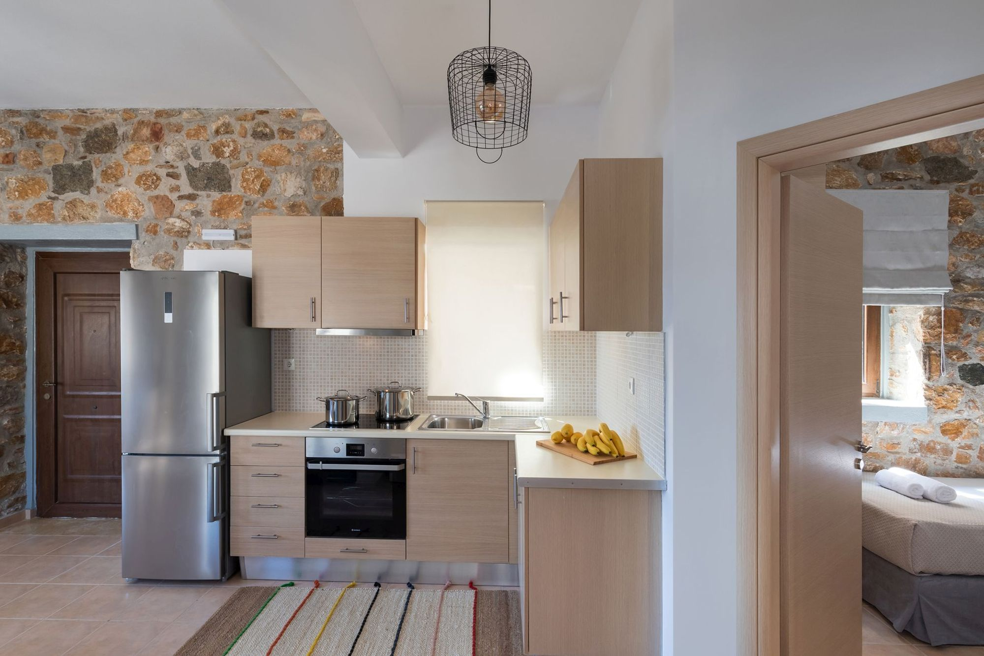 Modern kitchen in a stone built Syra Suite residence equipped with a big inox fridge and an electric cooker oven.