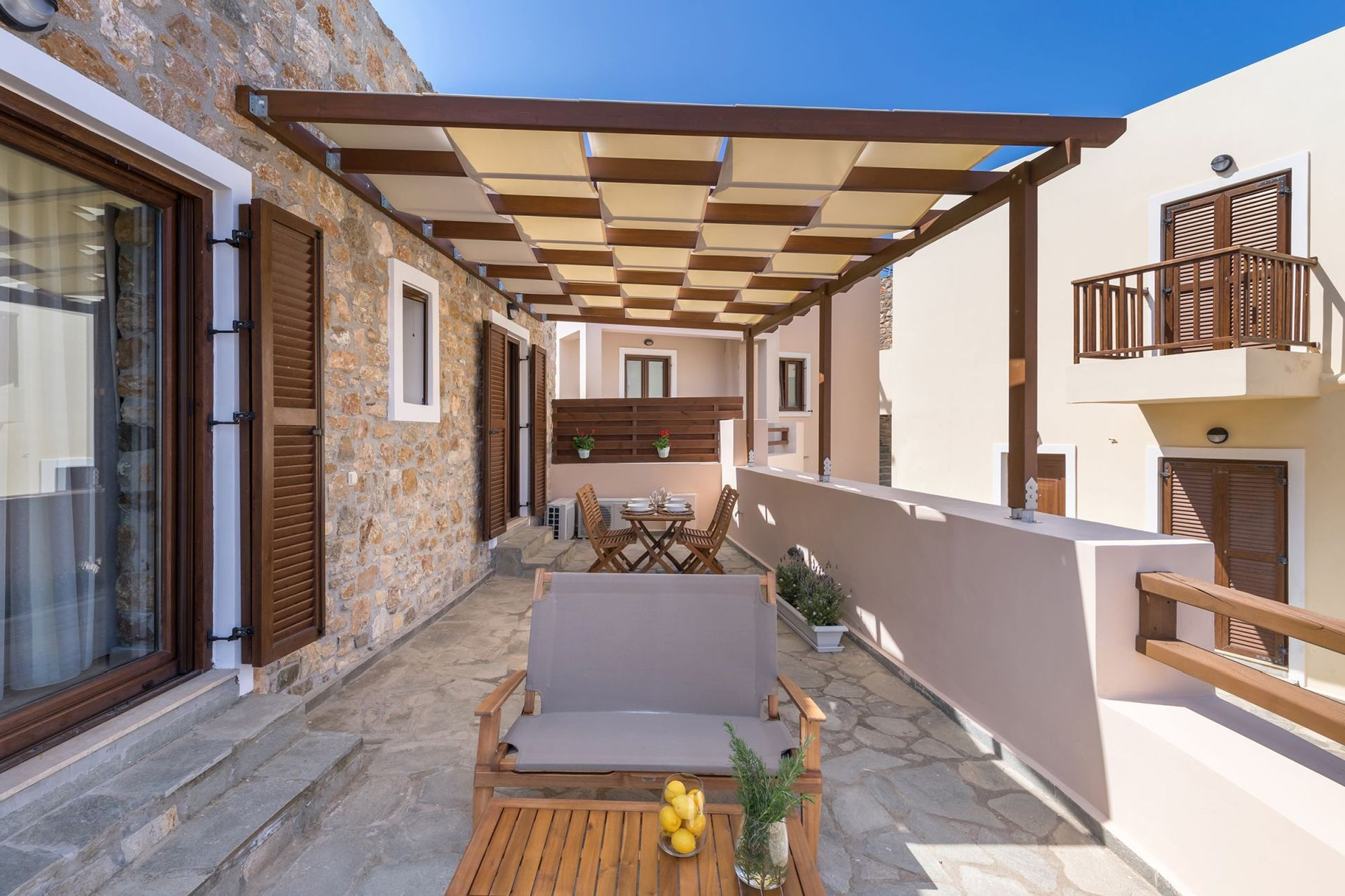 Veranda of a stone-built residence with pergola, furnished with a dining table and a lounge.